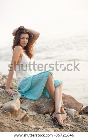 beautiful woman sitting on stone near water and holding hand on head