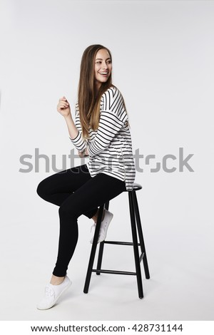 Beautiful woman sitting on stool, looking away