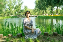 Beautiful woman sitting on the grass in the garden near lake