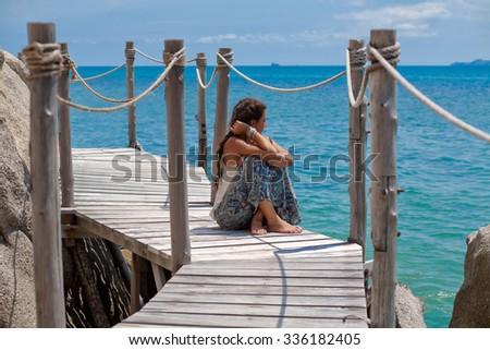 beautiful woman sitting on wooden bridge on tropical island