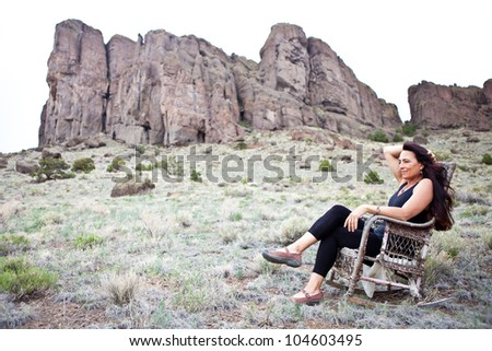 Beautiful Woman sitting out in Nature in a old Rocking Chair