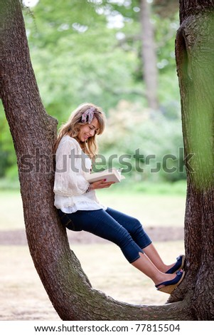 Beautiful woman sitting outdoors on a tree and reading a book