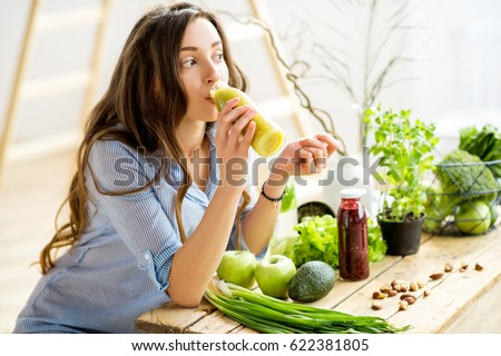 Beautiful woman sitting with healthy green food and drinking smoothie at home. Vegan meal and detox concept