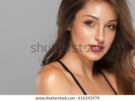 Beautiful Woman Skin Tanned Red Lips Healthy Beauty Skin Smile. Spa Beautiful Model Girl Cute Face over gray background. #616341974