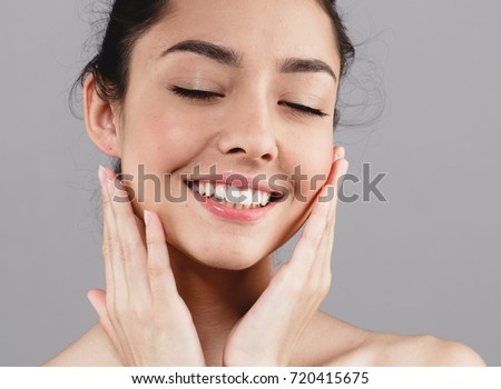 Beautiful woman skincare portrait with hand over gray background #720415675