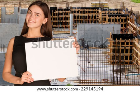 Beautiful woman smiling and hold empty paper sheet. Construction site as backdrop. Industrial concept