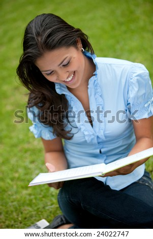 Beautiful woman smiling and studying outside with a notebook