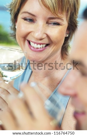 Beautiful woman smiling over a glass of wine as she sits at the dinner table socialising with her friends