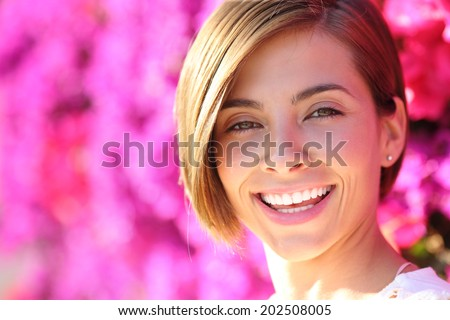 Beautiful woman smiling with white perfect teeth with a warmth lot of pink flowers in the background