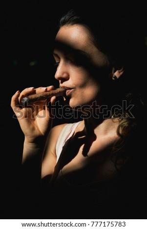Beautiful woman smoking a cigar. Cuban cigars concept
