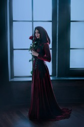 Beautiful woman stand near night window. Medieval mysterious queen holds rose in hands. Long red vintage dress hood. Gothic room. Carnival masquerade halloween costume. Dark lady witch royal evil plot