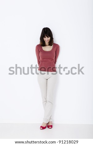 Beautiful woman standing and looking down. Studio shot.
