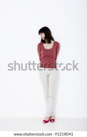 Beautiful woman standing and looking down. Studio shot.