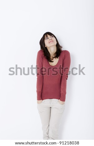 Beautiful woman standing and looking up. Studio shot.