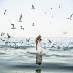 beautiful woman standing at the sea with seaguls around