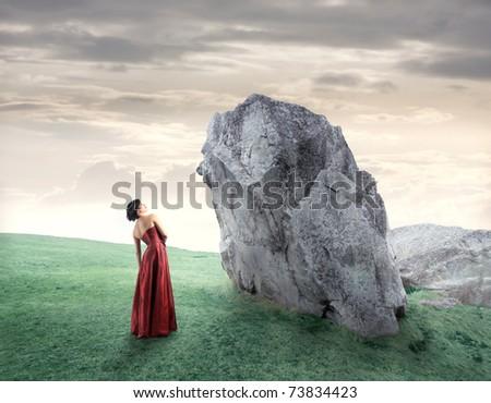 Beautiful woman standing beside a rock on a green meadow