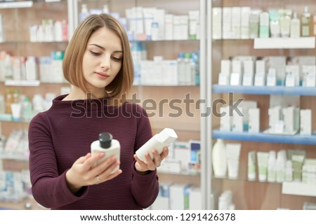 Beautiful woman standing in drugstore and choosing between two goods. Pharmacy customer holding in hands two white cosmetic bottles. Consuming of medical products.