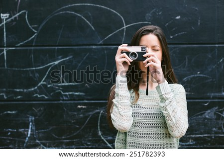 Beautiful woman standing in front a blackboard wall./ Young woman taking a photo with an old camera.