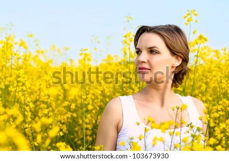 Beautiful woman standing in rapeseed field in bloom