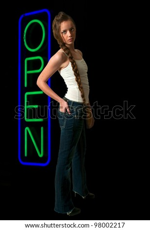 Beautiful woman standing next to a neon sign letting the world know that an establishment is open.