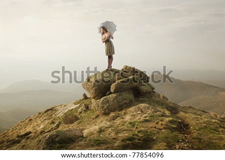 Beautiful woman standing on a stone and holding an umbrella - stock photo