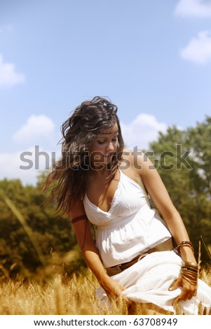 Beautiful woman standing on a wheat field outdoors on a hot summer afternoon. She is wearing a nice white dress and has long brown hair.