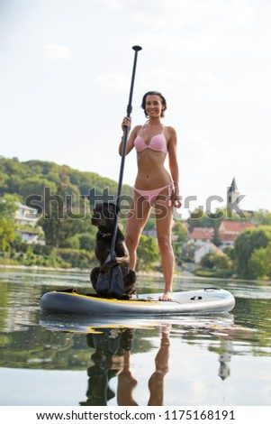 Beautiful woman standing on paddle board with her black dog.