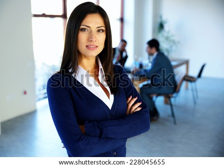 Beautiful woman standing with arms folded with colleagues on background