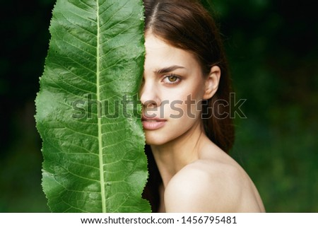 Beautiful woman stands behind a green large sheet of clean skin bare shoulders confident look nature #1456795481