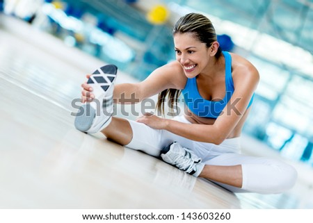 Beautiful woman stretching at the gym looking happy