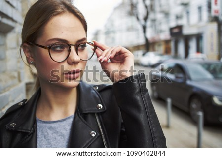 beautiful woman strolls down the street wearing glasses and a jacket