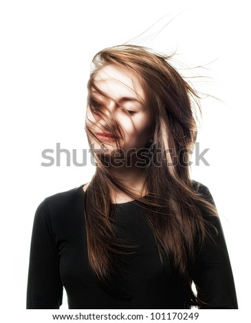 Beautiful woman studio portrait with wind on hair on face isolated on white