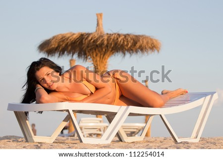 Beautiful woman sunbathing at the seaside on a daybed