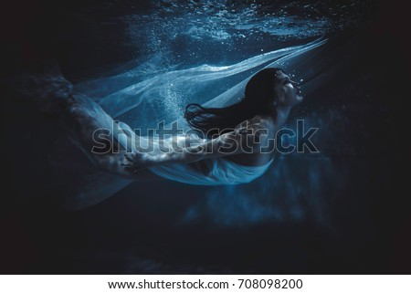 Beautiful woman swimming with fancy dress underwater