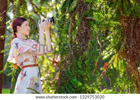 Beautiful woman taking a photo of foliage in a botanical garden with a digital camera