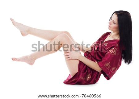 Beautiful woman taking care of her attractive legs, isolated on white