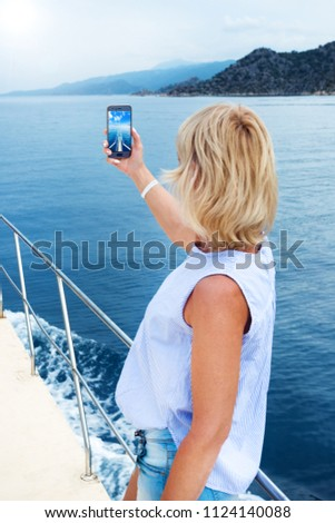 Beautiful woman taking photo on sailboat using smart phone technology for social media in ocean on luxury lifestyle adventure travel vacation. travel and active lifestyle concept #1124140088