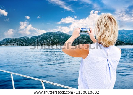 Beautiful woman taking photo on yacht  using smart phone technology for social media in sea on luxury lifestyle adventure travel vacation. travel and active lifestyle concept #1158018682