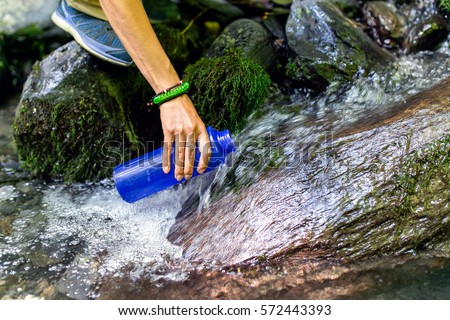 beautiful woman taking water from forest spring on hiking trip #572443393