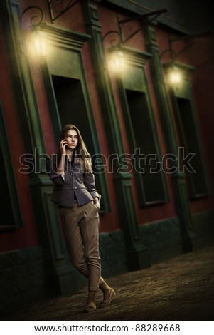 Beautiful woman talking on a cell phone in the night city