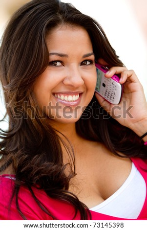 Beautiful woman talking on her cell phone and smiling