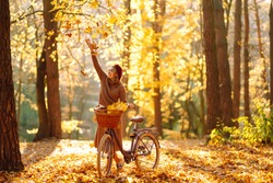 Beautiful Woman throws up autumn leaves and having fun  in autumn park. Relaxation, enjoying, solitude with nature.