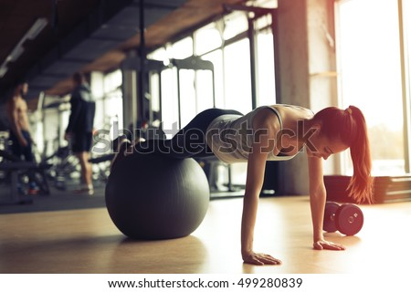 Beautiful woman training pilates in gym