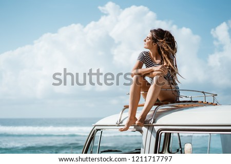 Beautiful woman travel by car and relaxing enjoy road trip nature sitting on the roof at summer day