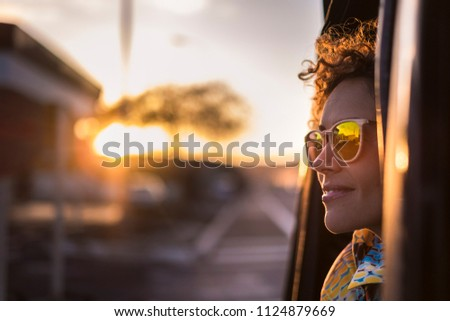 beautiful woman travel on a car looking outside and enjoy the light of the golden sunset on her face. nice lifestyle and peaceful emotions traveling around the world #1124879669
