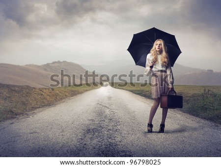Beautiful woman under an umbrella on a countryside road