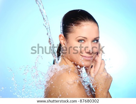 Beautiful woman under splash of water against blue background