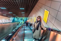Beautiful woman uses escalator to access Marmaray train in subway metro,Istanbul,Turkey.