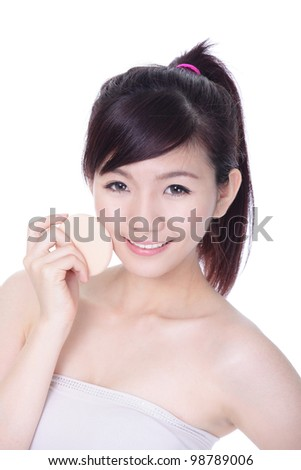 Beautiful Woman using cosmetic sponge on face with smile, isolated on white background, model is a asian beauty