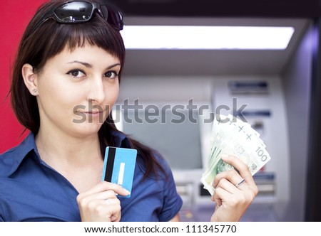 Beautiful woman using credit card, she is withdrawing money from an ATM machine.